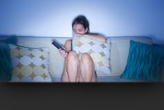 Young scared and panic Asian Chinese woman on her 20s watching horror movie on TV sitting at home living room sofa couch holding c Stock Images