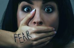 Young scared woman with black hair posing on camera. Scared brunette afraid. She look straight. Mouth closed with hand. Fear and despair. Isolated on blue stock image