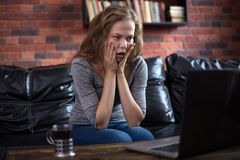 Young scared woman using a laptop, sitting on the couch and look at the screen. Reading bad news stock images