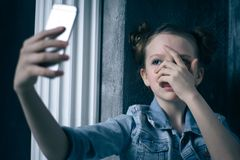 Young scared and worried teenager girl holding mobile phone as internet stalked victim abused and cyberbullying or cyber. Bullying stress concept in black Royalty Free Stock Photo