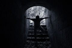 Young scary man enters dark stone tunnel Stock Photo