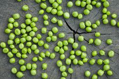 Young scattered green peas on a wooden background, stock photo