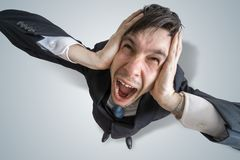 Young schizophrenic man suffers from headache and covering his ears with hands Royalty Free Stock Photo