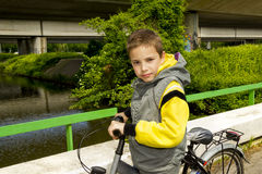 Young school boy with bicycle on the bridge. Young cute school boy with bicycle on the bridge Stock Images