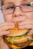 Young  school boy eating hamburger Royalty Free Stock Photos