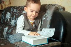 Young school boy in elegant suit. Learning something and read a book Royalty Free Stock Photography
