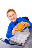 Young school boy with hamburger, isolated Royalty Free Stock Images