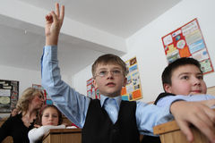 Young school boy. With one hand up to answer or ask a question. Picture taken in the first day of school in Resita, Romania Royalty Free Stock Photos