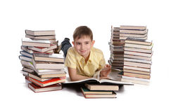Young school boy reading books. Young boy lies between a piles of books reading against a white background stock photo