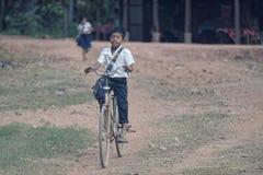 Young school boy riding bike, Bakong Temple, Cambodia Royalty Free Stock Photos