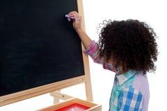 Young school child writing on blackboard Stock Image