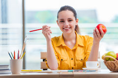 The young school gilr drawing pictures at home Royalty Free Stock Photos
