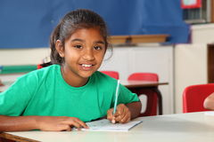 Young school girl 9 writing at her classroom desk Royalty Free Stock Images