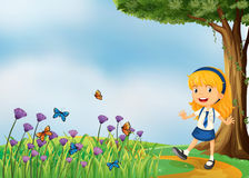 A young school girl in the garden with butterflies Stock Photo