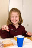 Young school girl eating lunch. A young school girl in her school uniform polo shirt, takes a break from eating lunch to smile for the camera. She appears to be Royalty Free Stock Photos