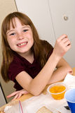 Young school girl eating lunch. A young school girl in her school uniform polo shirt, takes a break from eating lunch to smile for the camera. She appears to be Stock Images