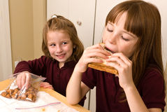 Young school girls eating lunch. A young school girl in her school uniform polo shirt, taking a bite of her sandwich, while a younger girls sneaks a pretzel. She Royalty Free Stock Images