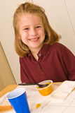 Young school girl eating lunch. A young school girl in her uniform polo shirt eating lunch. She appears to be eating a healthy lunch, containing a sandwich Stock Images