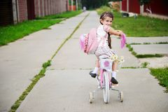 Young school girl with pink bagpack on a bicycle Royalty Free Stock Image