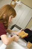 A young school girl preparing her lunch. A peanut butter and jelly sandwich. Slight selective focus used in attempt to bring attention to the knife and slice Royalty Free Stock Photos