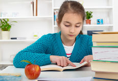 Young school girl reading a book. Royalty Free Stock Image
