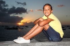 Young school girl sitting by the seaside at sunset Stock Image