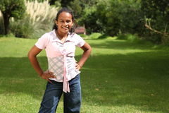 Young school girl standing in park hands on hips Royalty Free Stock Photos