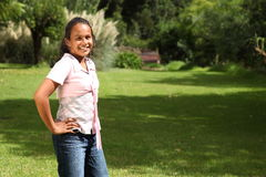 Young school girl standing in park hands on hips Royalty Free Stock Photo