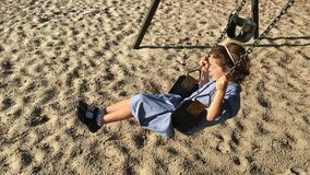 Young school girl swinging on a swing in school playground