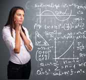 young school girl thinking about complex mathematical signs Royalty Free Stock Image