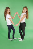 Young school girls holding hands and smiling at camera. Studio shot on green background Stock Photography