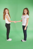 Young school girls holding hands and smiling at camera. Studio shot on green background Stock Photo