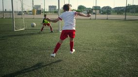 Young schoolboy football player scores goal running. With ball during junior league training stock video