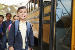 Young schoolboy and friends waiting to board the school bus royalty free stock photo