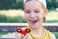 Young schoolboy holding popular fidget spinner toy - close up portrait. Happy smiling child playing with Spinner. Royalty Free Stock Photo