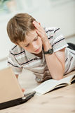 Young schoolboy lying on the floor studying Stock Images