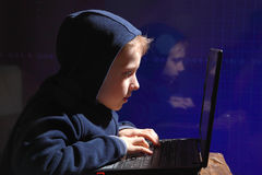 Young schoolboy prodigy - a hacker. Gifted student enters into the banking system. Hacker at work. Lots of digits on the computer screen. Criminal hacker Stock Photography