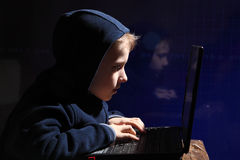Young schoolboy prodigy - a hacker. Gifted student enters into the banking system. Hacker at work. Lots of digits on the computer screen. Criminal hacker Stock Photos