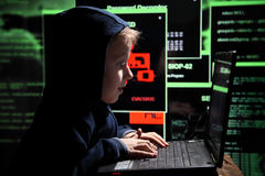 Young schoolboy prodigy - a hacker. Gifted student enters into the banking system. Hacker at work. Lots of digits on the computer screen. Criminal hacker Stock Images