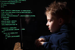 Young schoolboy prodigy - a hacker. Gifted student enters into the banking system. Hacker at work. Lots of digits on the computer screen. Criminal hacker Royalty Free Stock Photos
