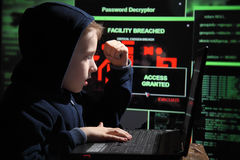 Young schoolboy prodigy - a hacker. Gifted student enters into the banking system. royalty free stock photo
