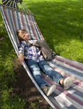 Young schoolboy resting. Young boy resting in a hammock after a day in school Stock Photography
