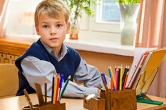 Young schoolboy sitting Behind a school desk Stock Photo