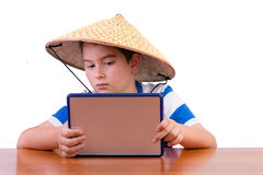 Young schoolboy studying in a Chinese hat Royalty Free Stock Photography