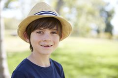 Young schoolboy in a sun hat smiling to camera, portrait stock photo