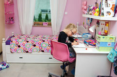 Young schoolgirl doing homework. A young schoolgirl (of six or seven years old) doing her homework in her pink color theme bedroom, sitting at her desk Stock Photo