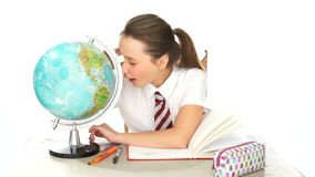 Young schoolgirl examining a world globe stock video