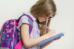 Young schoolgirl in glasses and with a backpack writes in a school notebook. Stock Photography