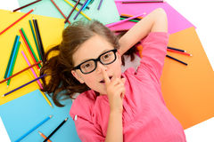Young schoolgirl with glasses lying on the floor amid of colored Stock Image