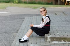 Young schoolgirl with glasses and school uniform outdoors in fro. Nt of school. School style Stock Photo